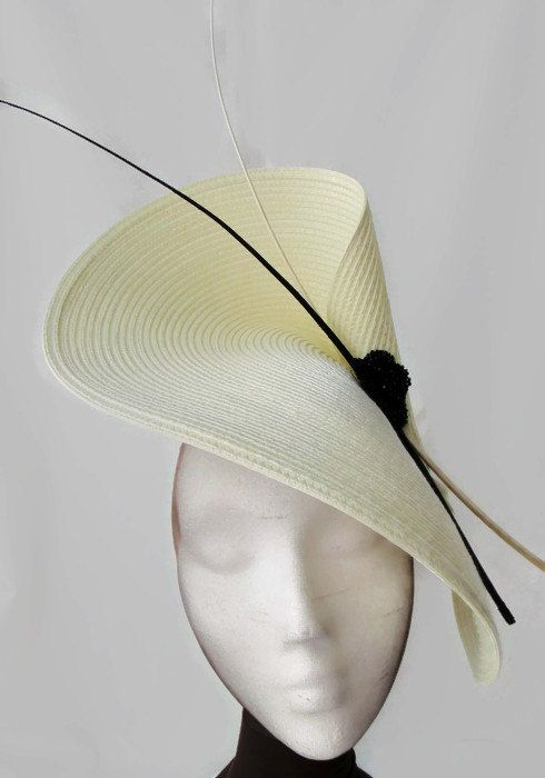 Black and white fascinator. It is a large fascinator very elegant. The base is in ivory color. The hat is decorated with a handmade flower of stones and
