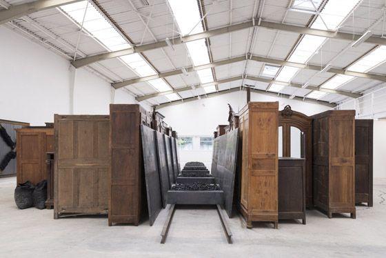 Jannis Kounellis, Senza Titolo, 2015, wardrobes, trunks, beams, sheet metal, coal, coal carts, 2 x 24 x 9 m. Galleria Continua Les Moulins 2015. Photo by Oak Taylor-Smith.