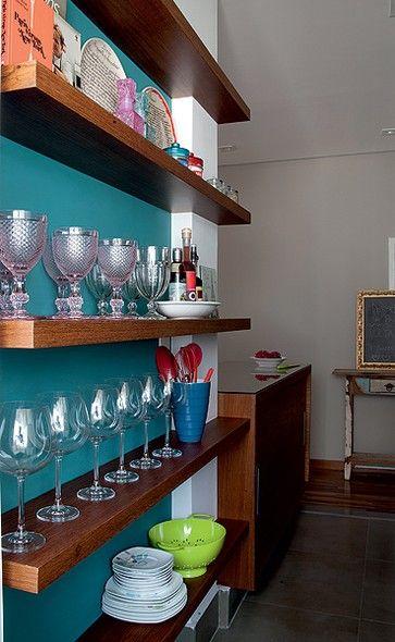 O apartamento de 60 m² tinha uma cozinha bem estreita. Em uma parede vazia, a arquiteta Gabriela Marques projetou prateleiras finas, onde a moradora expõe taças e vasos