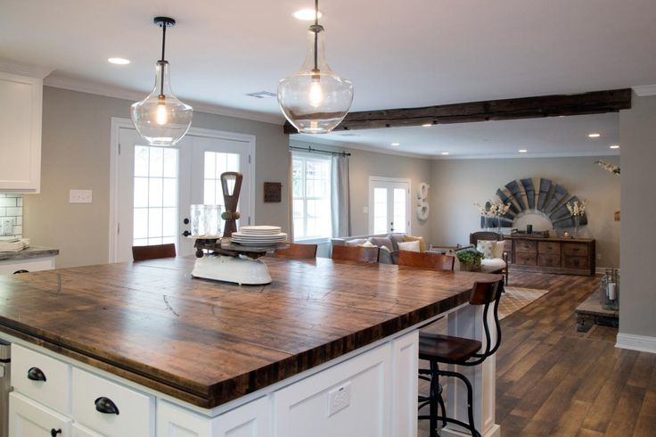 Two pendant lights illuminate a new kitchen island with a countertop made from the wood of an old train car.  The island offers additional counter space and a casual dining area.