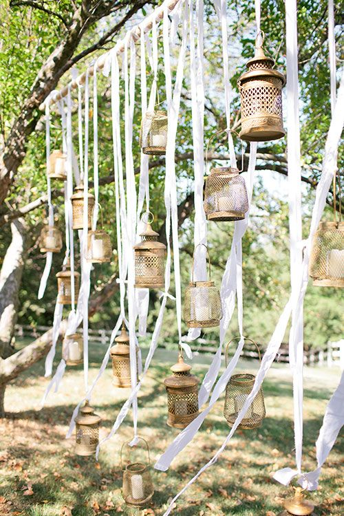 String vintage gold lanterns and ribbons between trees for an outdoor ceremony | @canarygrey | Brides.com