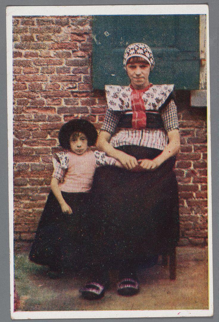 NEDERLANDSCHE KLEDERDRACHTEN 7. Bunschoten Vrouw en meisje voor een huis. 1920-1930 Zittende vrouw met gehaakte muts gedragen tot over de oren, het haar met pony, wit met paarse gesteven korte kraplap met een hele rode doek, geruite boormouwtjes, geruit stukje op donker schort, de twee ruiten zijn verschillend. Schoenen met zilveren gespen. Een staand meisje met pluummuts, kraplap, geruite boormouwtjes en lieffiessjullek, een donker schort met een geruit lijfje. #Utrecht #Spakenburg