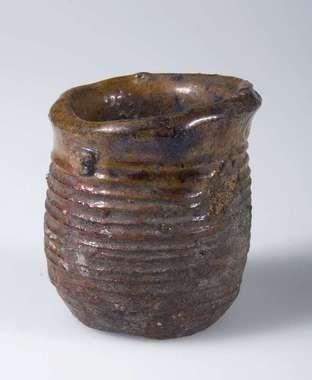 """Liten kopp av lergods. Koppen har räfflad utsida och är brunglaserad in- och utvändigt. Märkt """"B.623""""."""