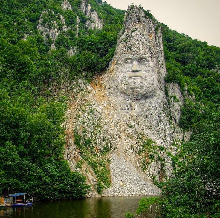 The rock sculpture of Decebalus is a 40 m high carving in rock of the face of Decebalus, the last king of Dacia, who fought against the Roman emperors Domitian and Trajan to preserve the independence of his country, which corresponded to modern Romania. The sculpture is on a rocky outcrop on the river Danube, at the Iron Gates, which form the border between Romania and Serbia. It is located near the city of Orşova in Romania. It is the tallest rock sculpture in Europe. Photo by valsangeorge