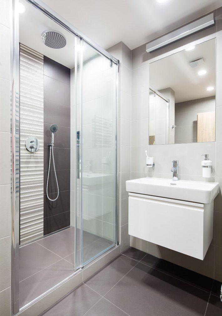 V koupelně jsou decentní velkoformátové obklady ve dvou odstínech šedé, ve sprchovém koutě je jako dekorace pás mozaiky.