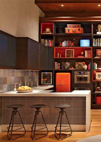 Loft + rio. O arquiteto Luiz Fernando Grabowsky idealizou seu espaço, misto de sala de estar, escritório e suíte, baseado em um morador sofisticado e versátil. A estante empilha módulos de diferentes tamanhos e acabamentos, como o padrão rovere (imita o tipo da madeira), no fundo, e a laca com brilho laranja e azul-marinho. Na cozinha, os azulejos da linha Vila Madá, da Portobello, exibem um mix de estampas. Os bancosPhilips, de Jader Almeida, se alinham à banca de Corian.