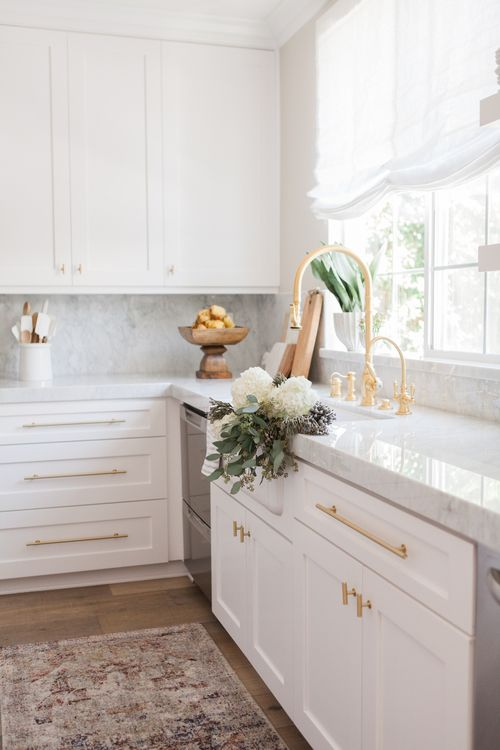 Lovely, light-washed kitchen with marble countertops, white cabinets & brass fixtures