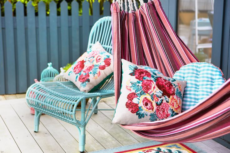 Striped hammock with floral and gingham cushions, patterned rug and green wicker seat, all by Carolyn Donnelly eclectic