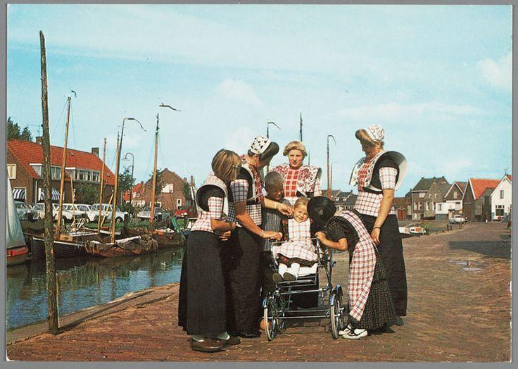 Drie vrouwen poseren in zomerdracht met witgebloemde kraplappen, geruite boormouwtjes en een schort met geruit stukje. Een jongen in boezeroen, een meisje blootshoofds met kulder en lieffiessjullek, een meisje met pluummuts met jurkje en fries schort en een meisje in wandelwagen met jurkje en friesschort zonder muts. 1970-1980 #Utrecht #Spakenburg