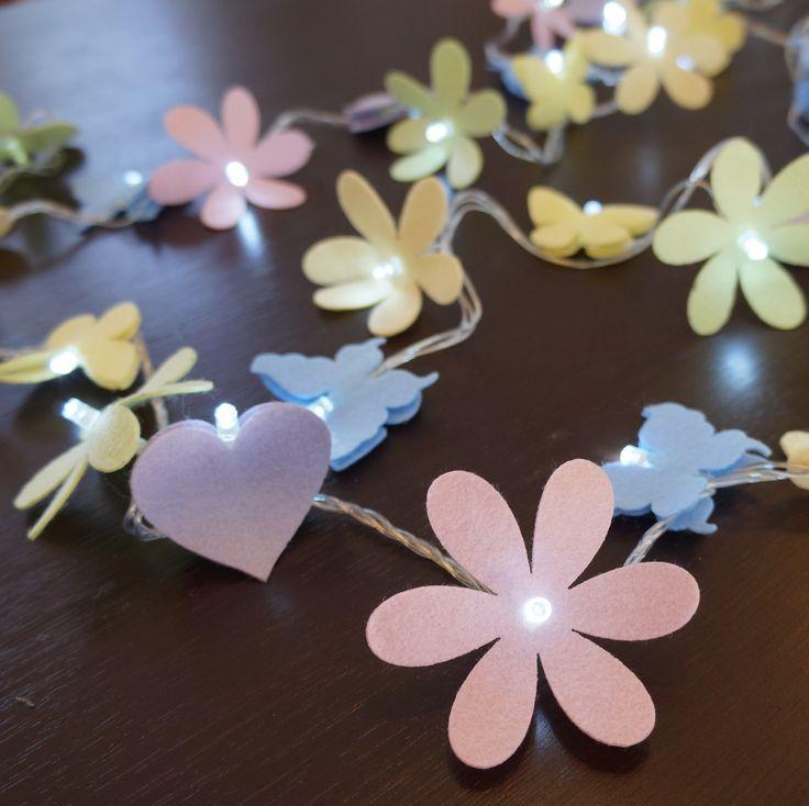 O quarto da sua filha, seu lavabo, seu espelho, sua escada...deixe-os com uma decoração exclusiva e moderna com o cordão luminoso de LED, ou luz de fada como é carinhosamente chamada. <br>Produzida com flores, corações e borboletas em feltro em cores claras. <br> <br>Comprimento aproximado = 7,3 m <br>Disponível apenas em 110v