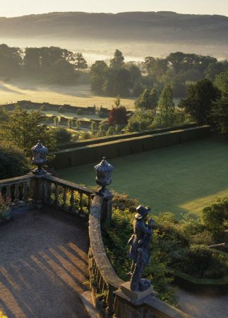 View from the Top Terrace in the garden at Powis Castle, Powys, Wales, UK, taken at dawn. The view shows the 17th century Italianate terraces below, as well as the architectural features and statues. The garden at Powis has survived the 18th century reaction against the formality of earlier garden design, and Powis is thus one of the few places in Britain where a true baroque garden may still be fully appreciated.