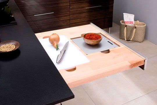 Astuce de rangement : une planche à découper et une balance intégrées dans le tiroir de la cusine.