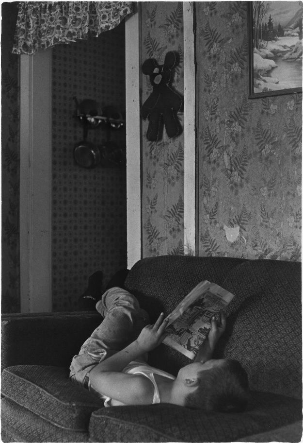 Boy lying on couch, reading comics. From the William Gedney Photographs and Writings.