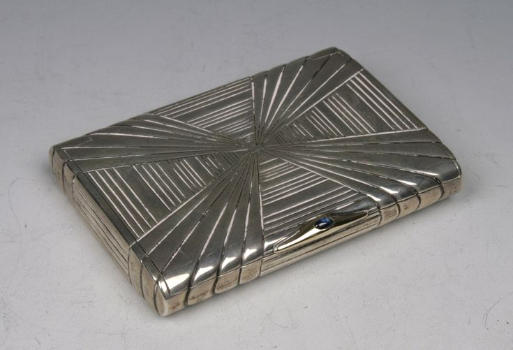 A CONTINENTAL ART DECO CIGARETTE CASE of rectangular form, with stylised geometric decoration, cabochon thumbpiece and gilt interior, marked 935 to the interior