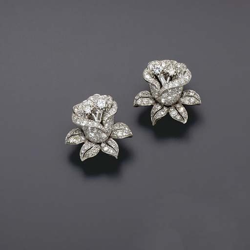 A  pair of ear clips, each designed as a pavé-set diamond flower, to the baguette and circular-cut diamond pistil, mounted in platinum