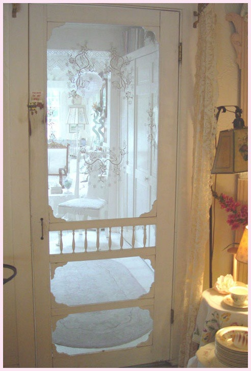 this old screen door is absolutely beautiful and is very welcoming as visitors enter this cottage home