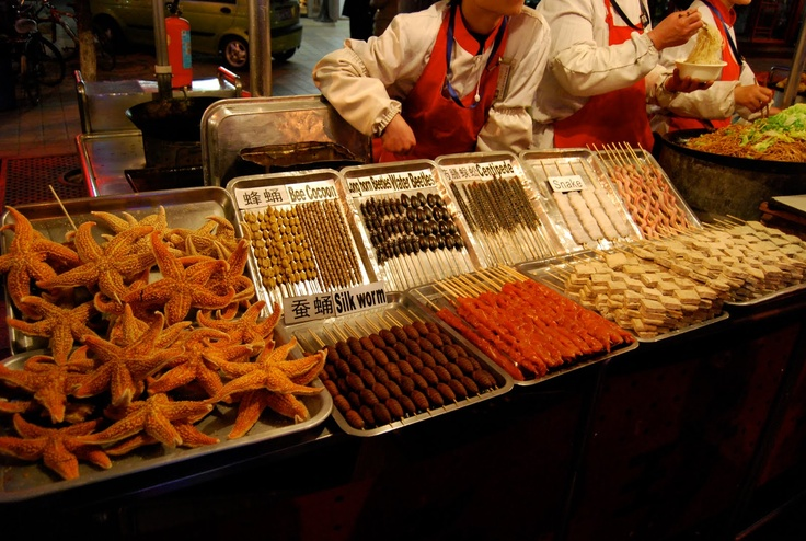 Okay, here they are. Let's see,  bee cocoon, long horn beetles, water beetles, centipedes, snakes, silk worm or star fish... on a stick! Welcome to  Donghuamen Night Market, Beijing, China! Who's the bravest?