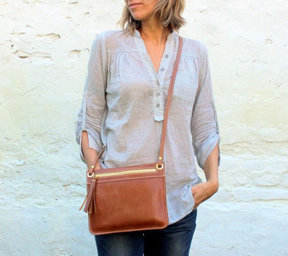 This brown leather cross body purse is perfect for a casual walk on the town. Not only does it looks stylish but it comes with plenty of storage to keep you organized and prepared anywhere you go. The brown leather cross body purse is a timeless classic and a must for any modern woman. Be sure to click through and see the amazing purses we are featuring.