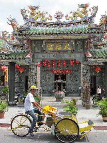 A rickshaw passes the Hainan Temple in Penang.
