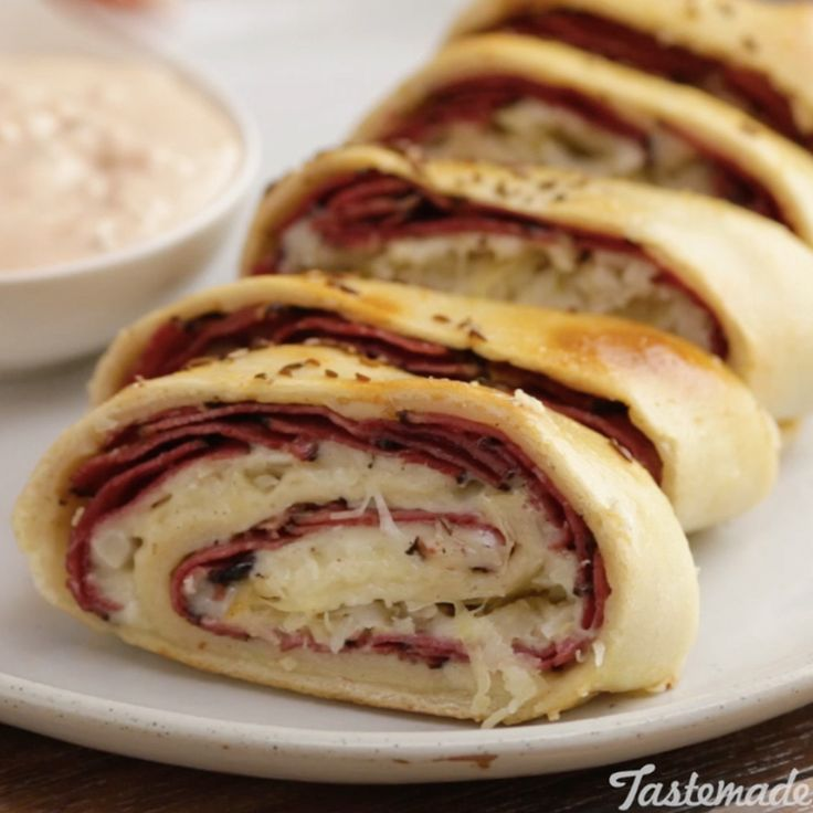 Recipe with video instructions: How to make Reuben Stromboli. Ingredients: 1 pizza dough ball, ¾ lb pastrami, sliced, 12 slices Swiss cheese, 12 oz sauerkraut, Egg for egg wash, 2 Tbsp caraway seeds, Russian dressing:, 1 cup mayo, ¼ cup ketchup, 2 Tbsp minced pickles, 1 Tbsp minced onion, 1 tsp Worcestershire
