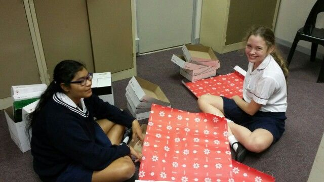 """Girls from WGHS doing community hours helping to wrap boxes for our """"Love box"""" drive"""
