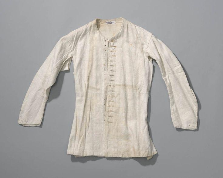 Wit linnen of katoenen (onder)hemdrok van een 18de eeuws model. In de 18de eeuw werden hemdrokken meestal gesloten met een enkele rij van talrijke knoopjes. Deze werden door nestelgaatjes gestoken. Aan de achterzijde werd een veter door de oogjes gehaald. Daar kwam geen naaien aan te pas. #NoordHolland #Zaanstreek