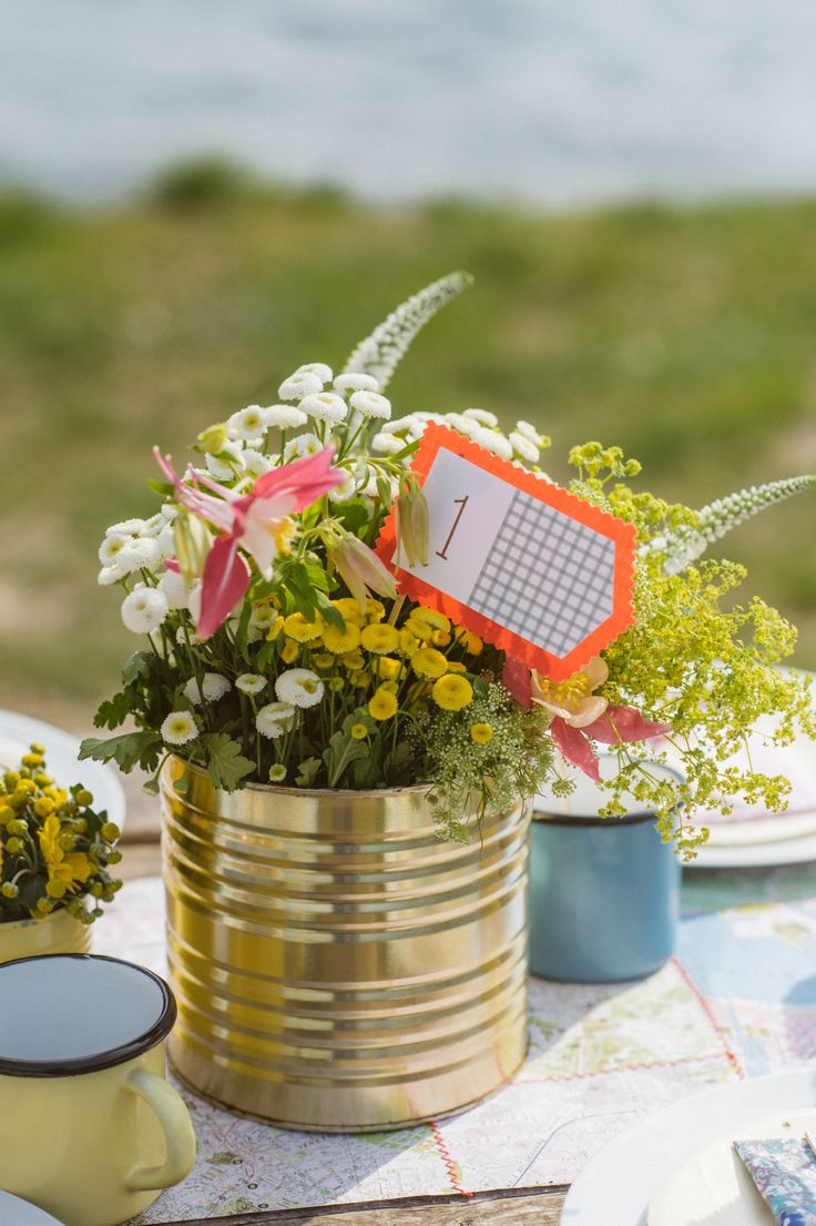 flower arrangement in tins and table number flag http://www.say-yep.com/issue1/