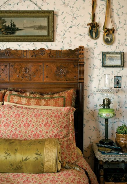 In the master bedroom, airy with a floral paper, Audry's own silk pillows sit on the Eastlake-style, spoon-carved walnut bed.