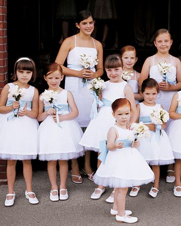 Pale Blue    Flower Girls    The flower girls at this Saratoga Springs, New York, wedding, all Theresa's nieces, carry lisianthius posies wrapped in blue-and-white ribbon and wear white Swiss-dot cotton dresses with blue sashes and tulle underlays by Jen Jen.