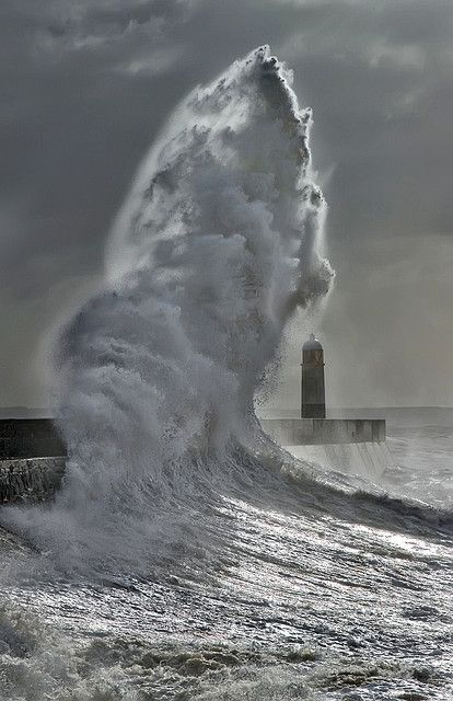 Grey: A giant wave crashes into the harbour wall at Porthcawl in South Wales. Photo - Steve Garrington