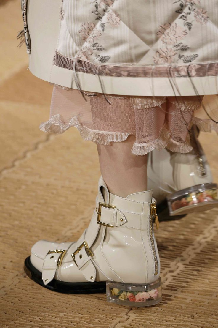 The three-buckle boot features multi-coloured silk rose buds inside a transparent block heel.