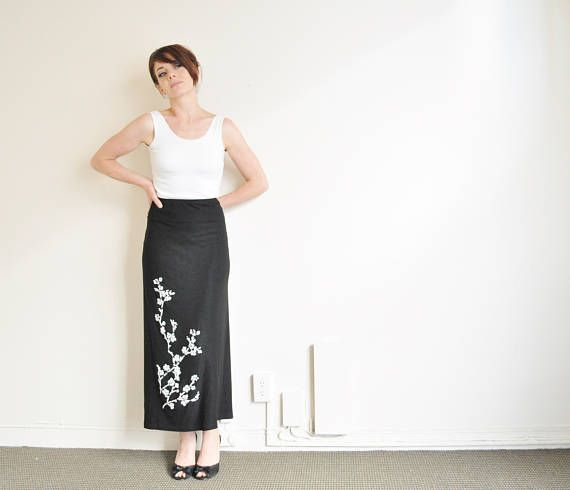 presenting. stretchy matte black fabric white beaded cherry blossom design tiny glued on beads, you know the kind high waist slim column style ankle length made of acetate and lycra unlined in lovely 1990s vintage condition except for a small repaired hole next to the back slit will fit a