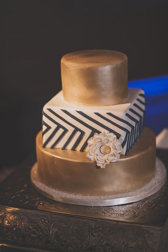 Three tier cake mixture of two gold round cakes and middle cake is square with blue and white design and a flower to make it complete | Justin Haugen Photography | villasiena.cc