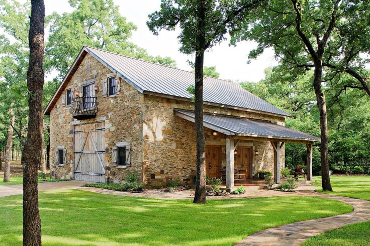 This barn by Heritage Restorations is an original, early Dutch barn, now restored in central Texas as a lakeside barn-style rustic game room and guest quarters. The large, operable front barn doors have vintage-designed, hand-forged iron strap hinges, and can be opened to join the interior living space and exterior porches.
