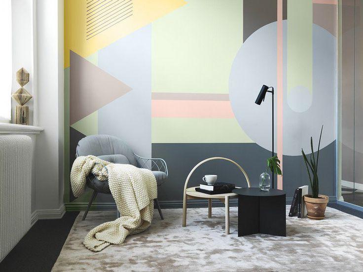 peinture décorative motif géométrique en couleurs pastel dans le coin café aménagé avec une chaise grise, une table basse en noir et bois