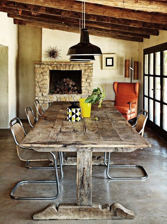 Rustic dining table with modern chairs, fireplace, and industrial light fixture