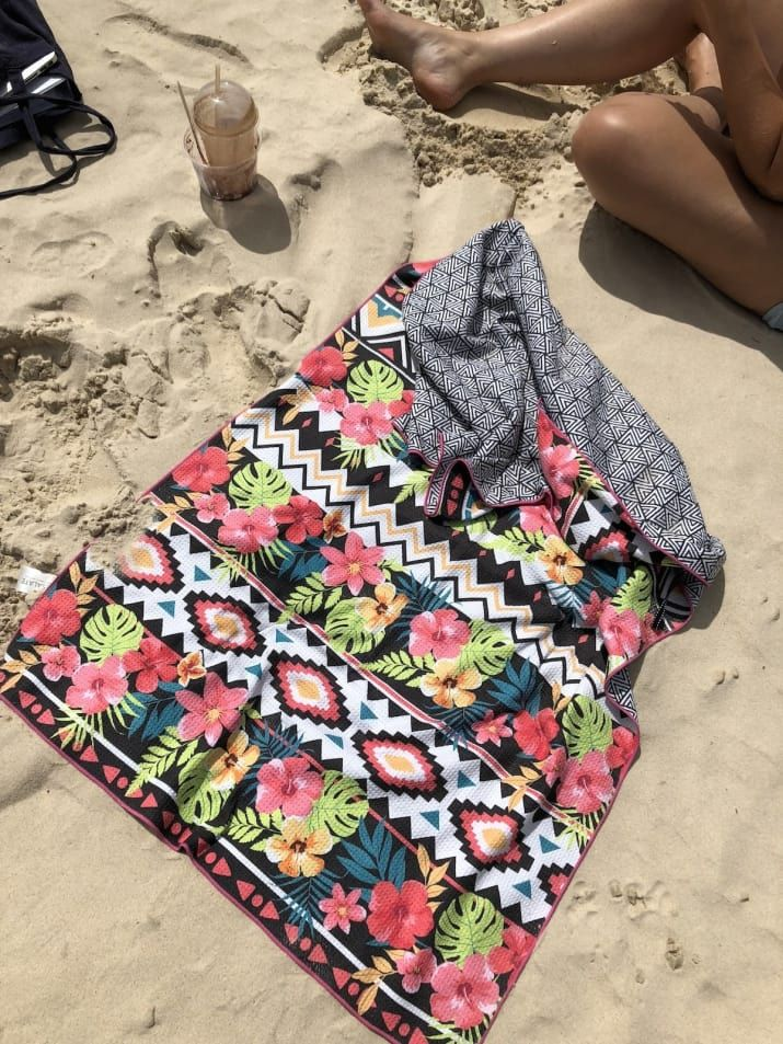 All the towels come with a colourful pattern on one side, and a black-and-white geometric pattern on the other. They're a bit flatter and less fluffy than a normal beach towel, but the size is good. I'm tall and could comfortably lie on it on the beach without hanging off the edges too much. I first tried it without getting it wet, just as a blanket to sit on the dry sand. It worked perfectly. When I was done, I shook it out and all the sand came off really easily. But I knew that when it…