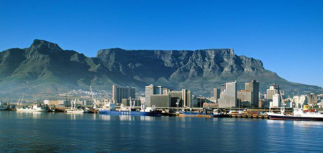 Table Mountain is a flat-topped granite and sandstone massif that rises 3,562 feet above Cape Town, South Africa.
