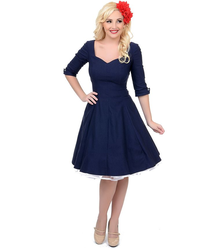 Your perfectly retro style doesn't have to hibernate once the weather gets colder, darling, so switch things up with this navy three quarter-sleeve Grace swing dress from Unique Vintage. This elegant 1950s-style vintage cocktail dress features three quarter-length sleeves with clear button detail on the cuffs. It is constructed from a thick yet comfortable fabric in a gorgeous shade of rich navy for a universally flattering appeal. Its sweetheart neckline and fitted bodice flatter your bust…