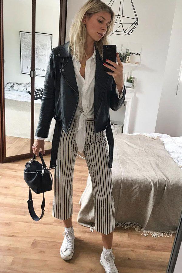 Lindsay Holland usa camisa branca com nó + calça cropped listrada e jaqueta de couro.
