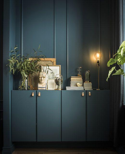 Twee IVAR kasten zijn in dezelfde kleur als de muur geschilderd; erop staan boeken, kunstwerken, planten en een lamp