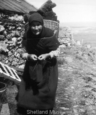 Shetland Museum Archives.    Woman with kishie of peats, knitting on steel wires. She wears a black or moorit hap around her shoulders and a woven headscarf.