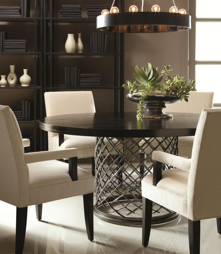 This round dining table features a hand-hammered metal base with a smooth table top