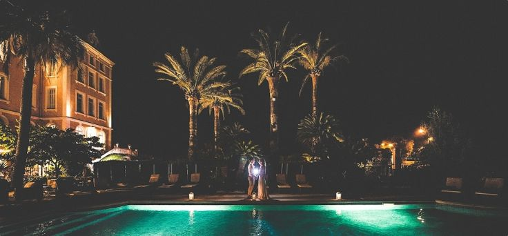 Bride and groom standing underneath the palm trees at night at the Hotel L