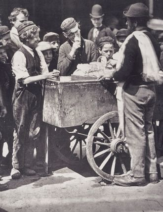 Children crowd around an Italian ice-cream seller and his cart. The image is taken from a series of 37 photographs published in the book, 'Street Life in London' (1877), with text written by John Thomson and the journalist Adolphe Smith.