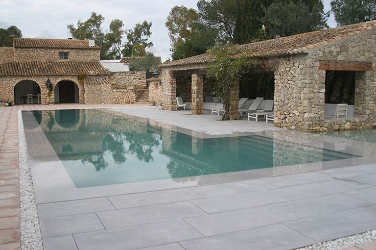 Carré d'Or catégorie piscine miroir - Carré Bleu C2F Piscines à Senlis (60) - Architecte : M. Guffroy - Piscine miroir en forme de L réalisée en béton armée avec un escalier maçonné sur la longueur. Dim. : 4 x 20 m + 8 x 4 m / Profondeur : 0.40 m / 1.50 m. Revêtement intérieur : carrelage Porcelanosa coloris gris. Plages en pierre reconstituée Porcelanosa.