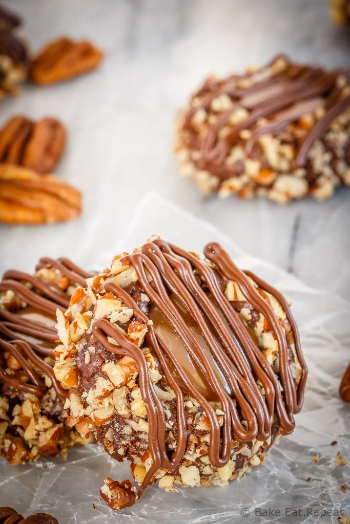 These turtle thumbprint cookies are amazing! Rich chocolate cookies rolled in chopped pecans, topped with salted caramel sauce and drizzled in chocolate! | Posted By: DebbieNet.com