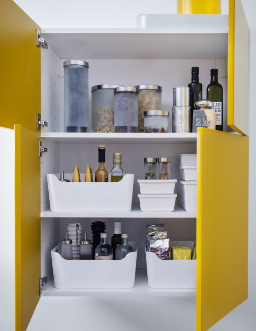 IKEA A kitchen cabinet with yellow doors is organized with white plastic bins.