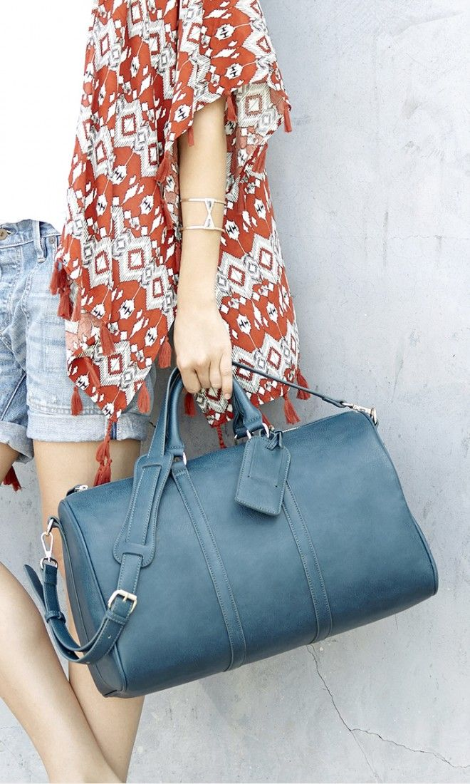 Teal weekender bag with an adjustable, detachable shoulder strap and removable luggage tag