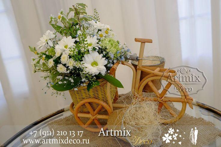 На регистрационном столике для жениха и невесты деревенского стиля велосипед и небольшие букетики из полевых цветов в оформлении свадебного торжества в стиле Рустик.